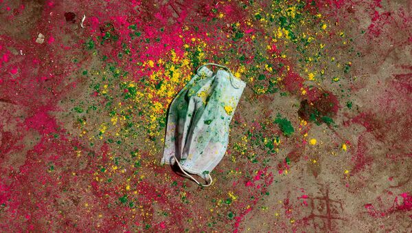 A face mask lies on a road covered with colour powder during Holi celebrations, amidst the spread of the coronavirus disease (COVID-19), in Chennai, India, March 29, 2021. - Sputnik International
