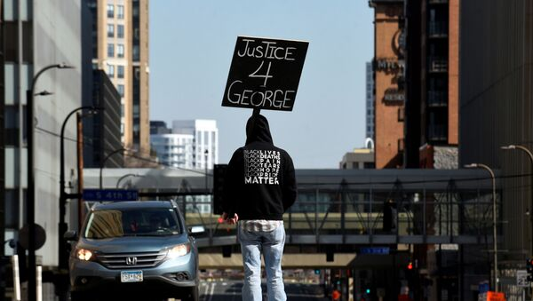 A demonstrator blocks traffic outside the Hennepin County Government Center during the first day of the trial of former police Derek Chauvin, who is facing murder charges in the death of George Floyd, in Minneapolis, Minnesota, U.S., March 29, 2021. - Sputnik International