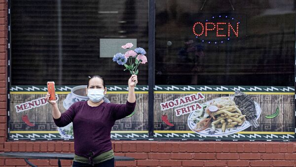 A woman holds plastic flowers as the motorcade of U.S. President Joe Biden drives past following a visits to the Centers for Disease Control and Prevention (CDC) in Atlanta, Georgia, U.S., March 19, 2021.  - Sputnik International