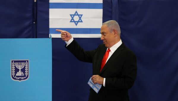 FILE PHOTO: Israeli Prime Minister Benjamin Netanyahu gestures while standing near a voting booth as he prepares to cast his ballot in Israel's general election, at a polling station in Jerusalem, 23 March 2021.  - Sputnik International