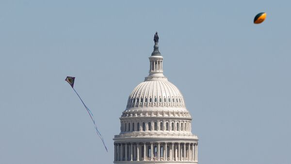 Kites and a football flies in the air near the U.S. Capitol as visitors gather to observe the annual cherry blossoms along the National Mall in Washington, U.S., March 29, 2021 - Sputnik International