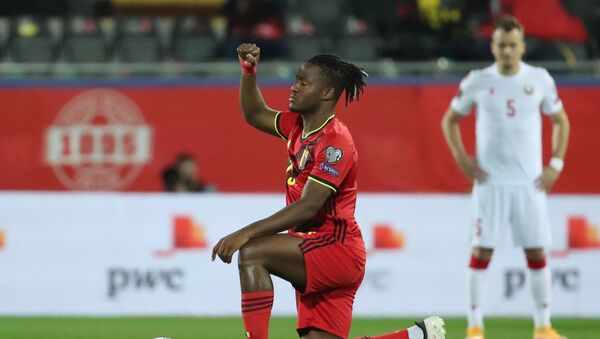 Belgium's Michy Batshuayi kneels in support of the Black Lives Matter campaign before the match - Sputnik International