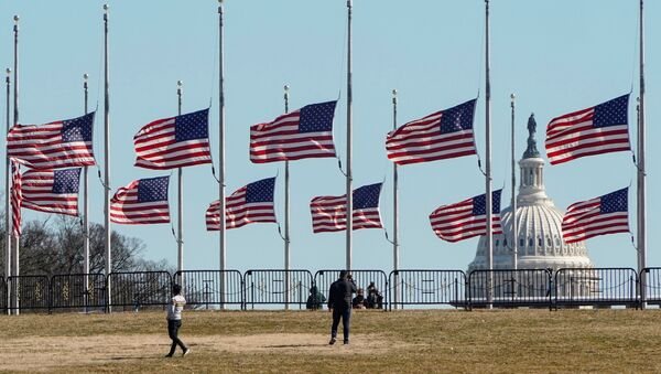 People walk past flags flying at half staff at the Washington Monument in memory of 500,000 deaths due to coronavirus disease (COVID-19) in Washington, U.S., February 24, 2021. - Sputnik International