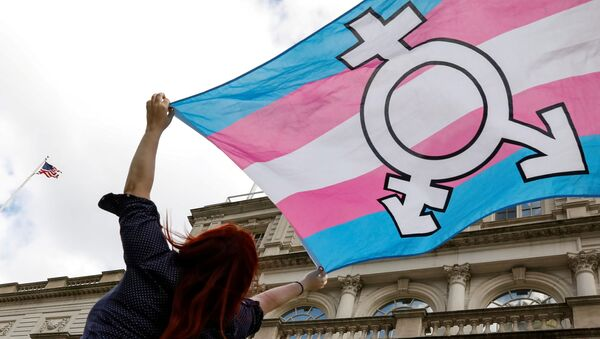 FILE PHOTO: A person holds up a flag during rally to protest the Trump administration's reported transgender proposal to narrow the definition of gender to male or female at birth, at City Hall in New York City, U.S., October 24, 2018. - Sputnik International