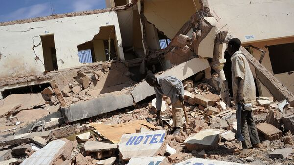 In this file photo children search on February 5, 2013 in the ruins of a hotel destroyed by French air strikes in  Douentza, as he town was retaken by French and Malian troops in January. - Sputnik International