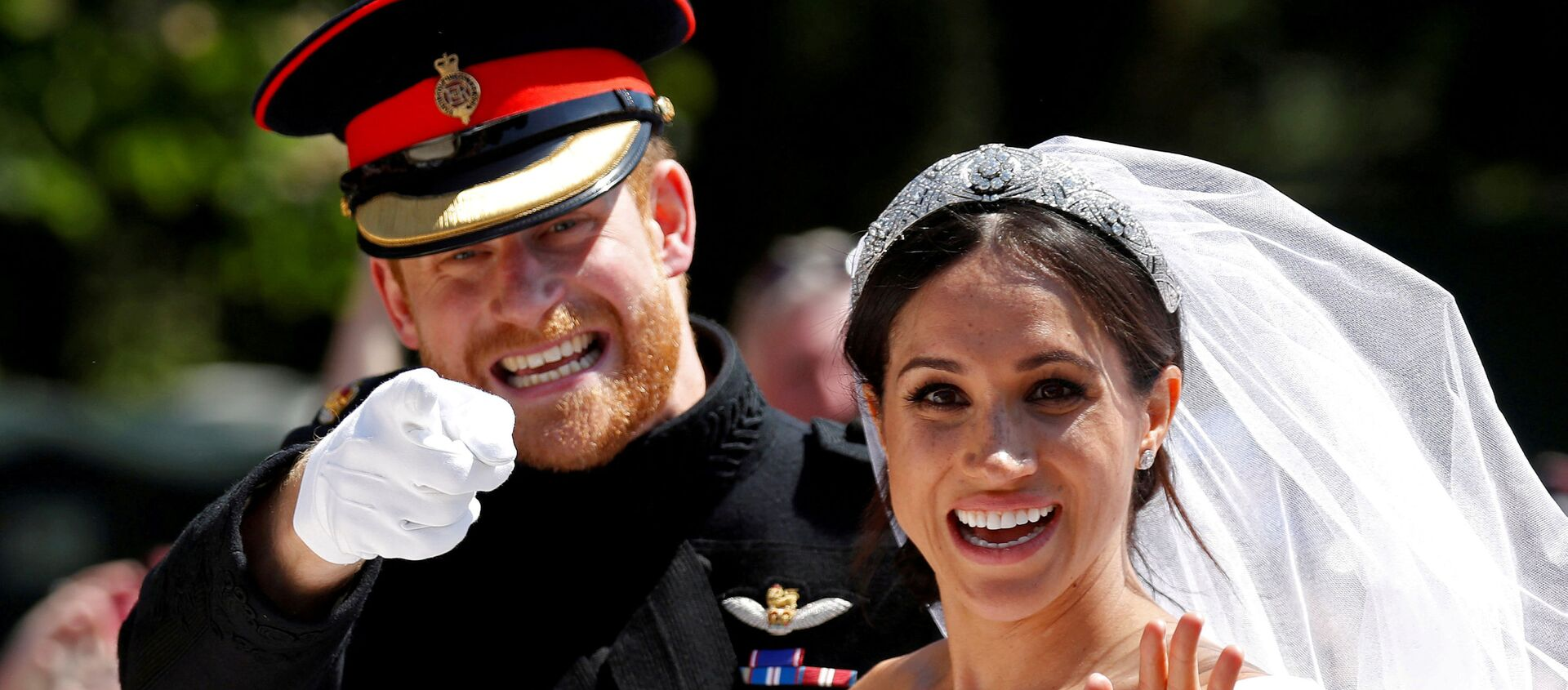 Britain's Prince Harry gestures next to his wife Meghan as they ride a horse-drawn carriage after their wedding ceremony at St George's Chapel in Windsor Castle in Windsor, Britain, May 19, 2018. - Sputnik International, 1920, 17.04.2021