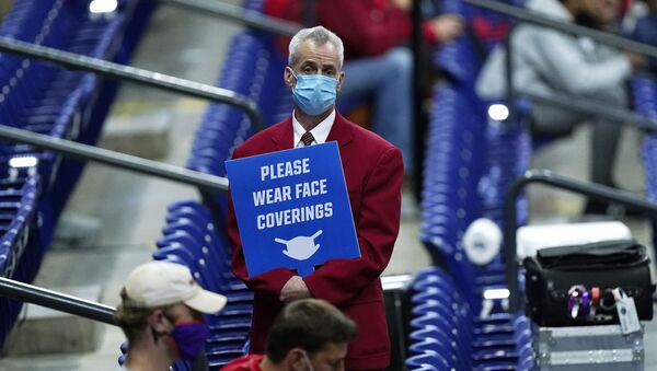 In this March 21, 2021, file photo, an usher holds a sign reminding fans to wear masks during a college basketball game between Houston and Rutgers in the second round of the NCAA tournament at Lucas Oil Stadium in Indianapolis - Sputnik International
