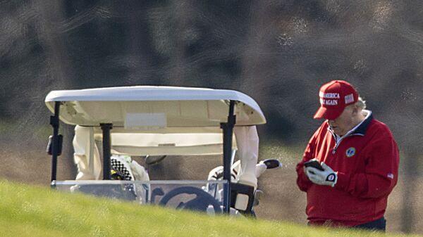 US President Donald Trump makes a phone call as he golfs at Trump National Golf Club on 26 November 2020 in Sterling, Virginia. - Sputnik International
