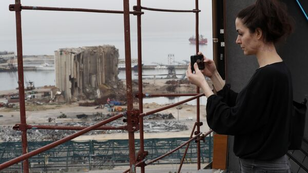 Joana Dagher, 33, who lost her memory for two full months from the trauma she suffered in the massive August explosion at the Beirut port, including a cerebral contusion and brain lesions, takes pictures of the explosion scene from her damaged apartment rooftop, in Beirut, Lebanon, Wednesday, Jan. 27, 2021. - Sputnik International