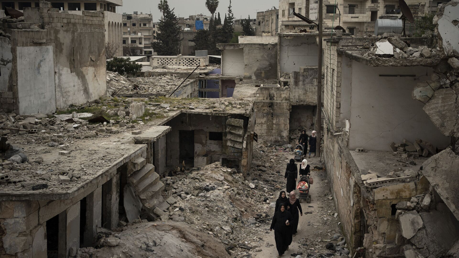 In this March 12, 2020 file photo, women walk in a neighborhood heavily damaged by airstrikes in Idlib, Syria. - Sputnik International, 1920, 14.10.2021