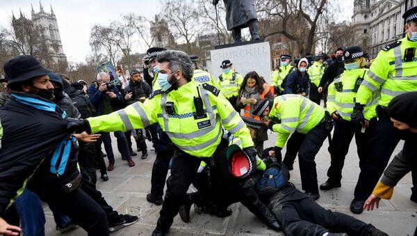 Police officers restrain demonstrators during a protest in London, Britain, April 3, 2021. REUTERS/Toby Melville  - Sputnik International