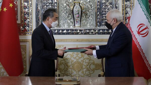 Iranian Foreign Minister Mohammad Javad Zarif (R) and his Chinese counterpart Wang Yi, are pictured during the signing of an agreement in the capital Tehran, on March 27, 2021. - Sputnik International