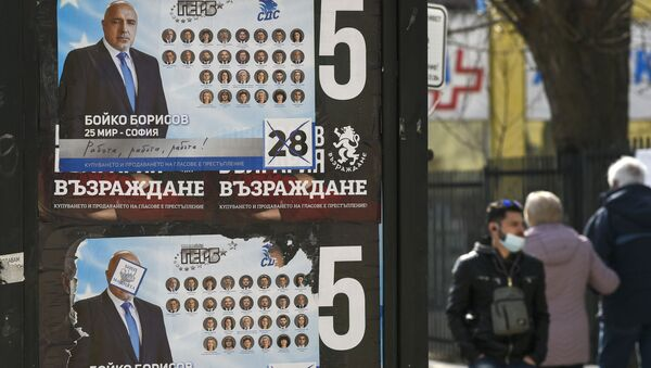 People walk past election posters of Bulgarian Prime Minister and leader of centre-right GERB party Boyko Borissov in Bankya on April 2, 2021, ahead of the General elections in two days. - Bulgarians will go to the polls on April 4, to elect a new parliament, with Prime Minister Boyko Borisov's centre-right party tipped to finish first despite a wave of anti-government protests last summer. While the latest polls give Borisov's GERB party an average lead of eight percentage points over the main opposition Socialists, analysts still expect the next parliament to be marked by more instability. - Sputnik International