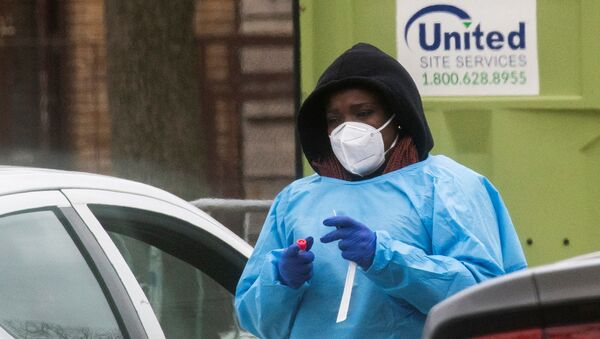 A health worker prepares to do a coronavirus disease (COVID-19) test as people wait at a drive-through COVID-19 testing center in a local street, in Newark, New Jersey, U.S - Sputnik International