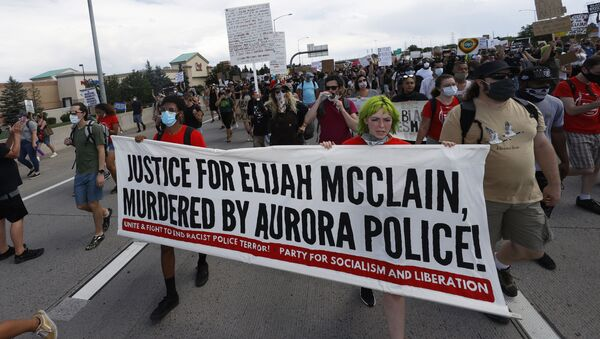Demonstrators carry a banner while marching down Interstate 225 during a rally and march over the death of 23-year-old Elijah McClain, Saturday, June 27, 2020, in Aurora, Colo. McClain died in late August 2019 after he was stopped while walking to his apartment by three Aurora Police Department officers. - Sputnik International