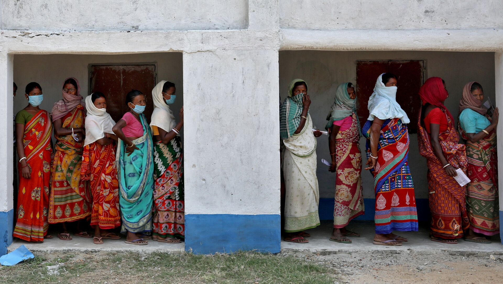 Women wait in line to cast their vote at a polling booth during the first phase of West Bengal's state election in Purulia district, India - Sputnik International, 1920, 06.04.2021