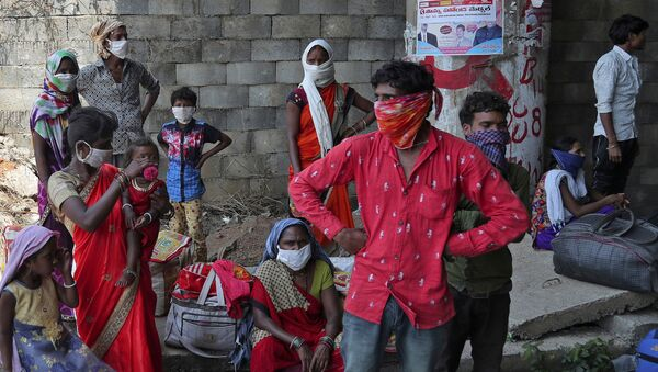 Migrant workers from the state of Maharashtra trying to return to their villages hundreds of miles away, take a break as they walk during a nationwide lockdown to curb the spread of new coronavirus on the outskirts of Hyderabad, India, Monday, 4 May 2020. - Sputnik International