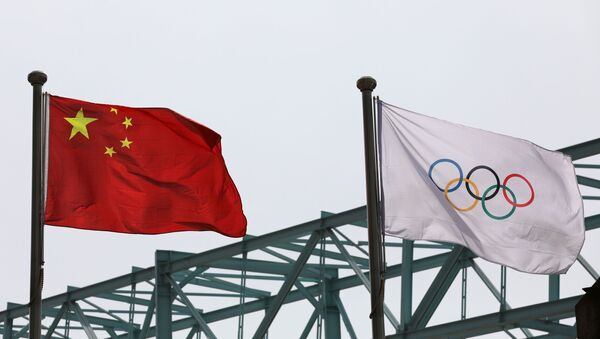 A Chinese national flag flutters next to an Olympic flag at the Beijing Organising Committee for the 2022 Olympic and Paralympic Winter Games, in Beijing, China March 30, 2021 - Sputnik International