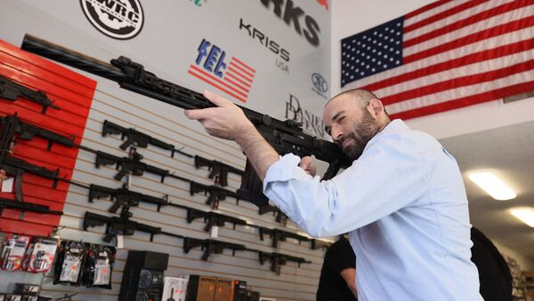 """Austin Title handles a weapon as he visits WEX Gunworks on March 24, 2021 in Delray Beach, Florida. U.S. President Joe Biden has called on lawmakers to """"immediately pass"""" legislation to help curb gun violence in the county.   - Sputnik International"""