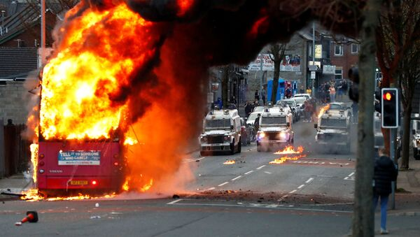 Police vehicles are seen behind a hijacked bus burns on the Shankill Road as protests continue in Belfast, Northern Ireland, 7 April 2021 - Sputnik International