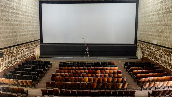 A worker cleans the screen of a cinema hall as part of preparations for a possible reopening after the government eased the lockdown restrictions previously imposed due to the Covid-19 coronavirus, in Chennai on October 8, 2020 - Sputnik International