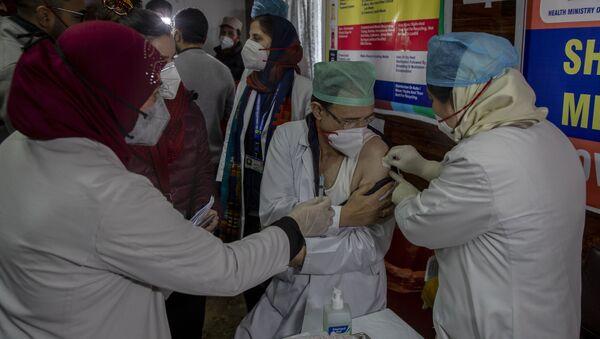 A Kashmiri doctor receives a COVID-19 vaccine at a government Hospital in Srinagar, Indian controlled Kashmir, Saturday, 16 January 2021 - Sputnik International