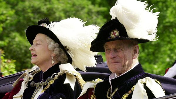 FILE PHOTO: Britain's Queen Elizabeth II and Prince Phillip, the Duke of Edinburgh, wearing their Order of the Garter robes, ride in an open-topped carriage to Windsor Castle - Sputnik International
