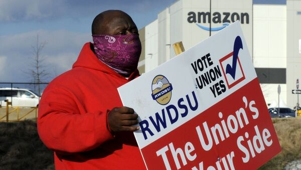 FILE - In this Tuesday, Feb. 9, 2021, file photo, Michael Foster of the Retail, Wholesale and Department Store Union holds a sign outside an Amazon facility where labor is trying to organize workers in Bessemer, Ala. - Sputnik International