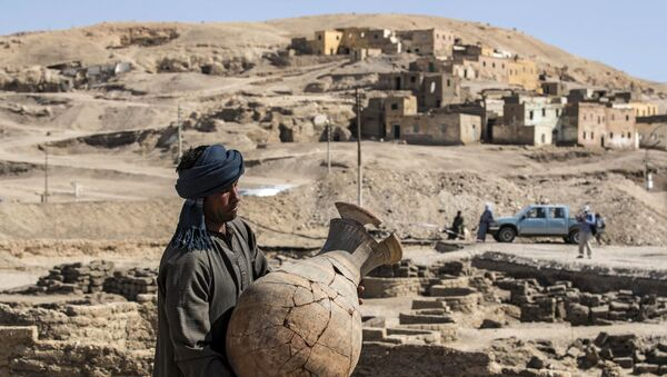 A picture taken on April 10, 2021, shows a worker carrying a pot at the archaeological site of a 3000 year old city, dubbed The Rise of Aten, dating to the reign of Amenhotep III, uncovered by the Egyptian mission near Luxor. - Archaeologists have uncovered the remains of an ancient city in the desert outside Luxor that they say is the largest ever found in Egypt and dates back to a golden age of the pharaohs 3,000 years ago. Famed Egyptologist Zahi Hawass announced the discovery of the lost golden city, saying the site was uncovered near Luxor, home of the legendary Valley of the Kings.  - Sputnik International