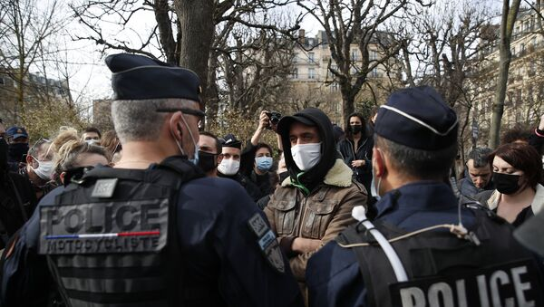 A man faces police officers during a counter-protest while supporters of the group Generation Identity demonstrate, Saturday, Feb. 20, 2021 in Paris. Supporters of Europe's extreme-right, anti-migrant movement Generation Identity protest against French government efforts to shut it down as a racist militia. - Sputnik International