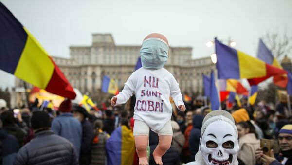 A man wearing a skull mask while dressed in white protection gear holds a baby doll with the message I am not a lab rat during a protest against mandatory mask wearing and coronavirus disease (COVID-19) vaccination, near the Romanian Parliament, in Bucharest, Romania March 20, 2021. - Sputnik International