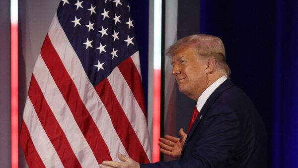 Former President Donald Trump embraces the American flag as he arrives on stage to address the Conservative Political Action Conference held in the Hyatt Regency on 28 February 2021 in Orlando, Florida. Joe Raedle/Getty Images/AFP (Photo by JOE RAEDLE / GETTY IMAGES NORTH AMERICA / Getty Images via AFP) - Sputnik International