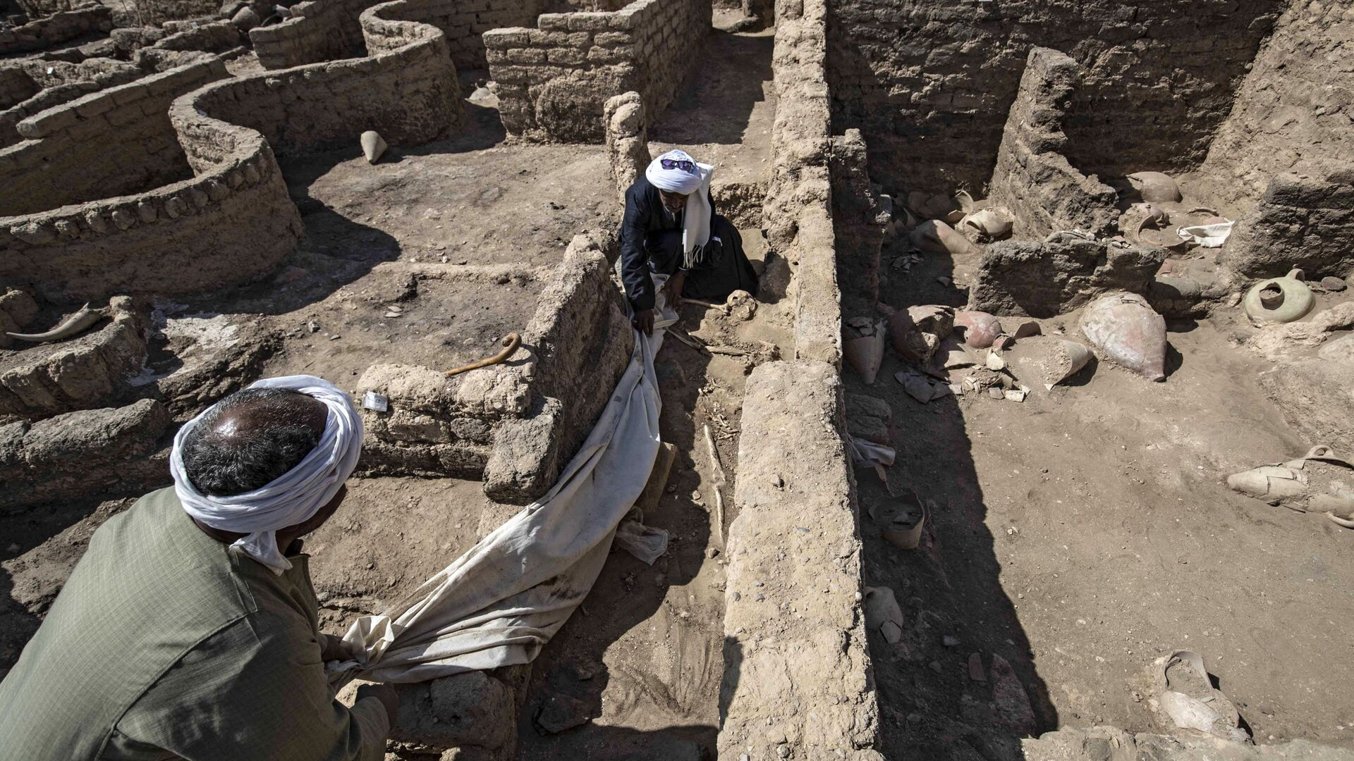 A picture taken on April 10, 2021, shows workers at the archaeological site of a 3000 year old city, dubbed The Rise of Aten, dating to the reign of Amenhotep III, uncovered by the Egyptian mission near Luxor. - Archaeologists have uncovered the remains of an ancient city in the desert outside Luxor that they say is the largest ever found in Egypt and dates back to a golden age of the pharaohs 3,000 years ago. Famed Egyptologist Zahi Hawass announced the discovery of the lost golden city, saying the site was uncovered near Luxor, home of the legendary Valley of the Kings.  - Sputnik International, 1920, 25.09.2021