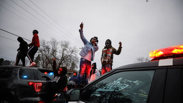 Demonstrators stand on a police vehicle during a protest after police allegedly shot and killed a man, who local media report is identified by the victim's mother as Daunte Wright, in Brooklyn Center, Minnesota, U.S. - Sputnik International