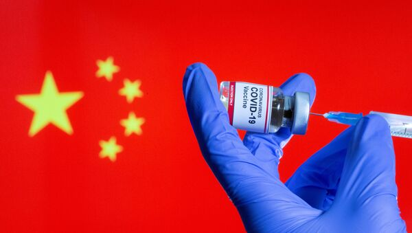 FILE PHOTO: FILE PHOTO: A woman holds a small bottle labeled with a Coronavirus COVID-19 Vaccine sticker and a medical syringe in front of displayed China flag in this illustration taken, October 30, 2020 - Sputnik International