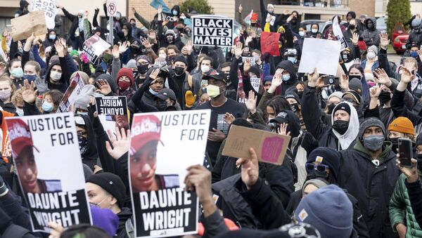 People gather before curfew holding pictures of Daunte Wright along with Black Lives Matter signs to protest his death by a police officer in Brooklyn Center, Minnesota on April 12, 2021.  - Sputnik International