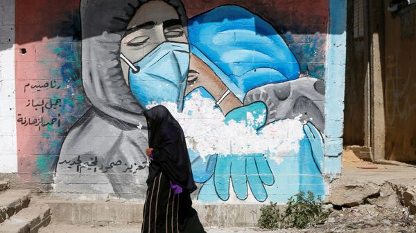 A Palestinian woman walks past a mural, amid the coronavirus disease (COVID-19) outbreak, in the central Gaza Strip March 17, 2021. Picture taken March 17, 2021 - Sputnik International