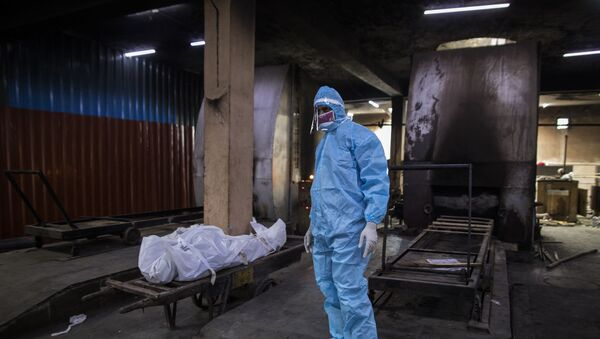 A relative wearing Personal Protective Equipment (PPE) stands next to the body of a person who died from the COVID-19 coronavirus before cremation in a furnace at the Nigambodh Ghat cremation ground, in New Delhi on August 22, 2020. - Sputnik International
