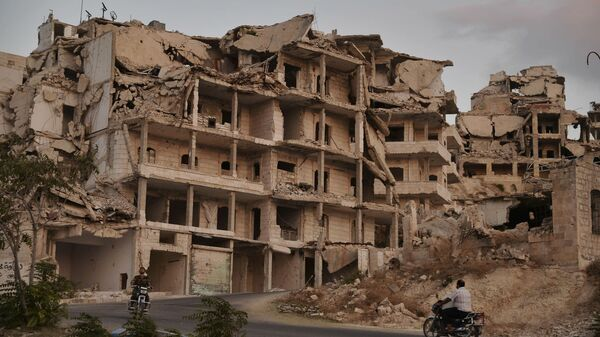 In this Thursday, Sept. 20, 2018, file, photo, motor cycles ride past buildings destroyed during the fighting in the northern town of Ariha, in Idlib province, Syria. - Sputnik International