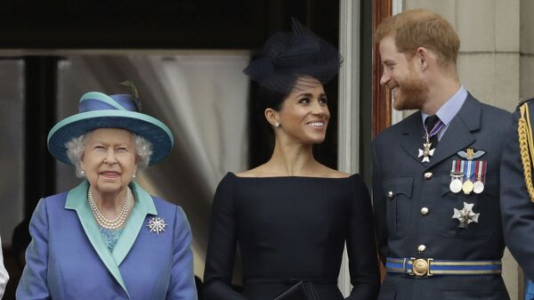 In this Tuesday, July 10, 2018 file photo Britain's Queen Elizabeth II, and Meghan the Duchess of Sussex and Prince Harry watch a flypast of Royal Air Force aircraft pass over Buckingham Palace in London. - Sputnik International