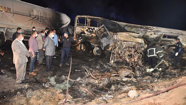 In this photo provided by Assiut Governorate media office, the authorities work on the collision site where a bus overturned Tuesday, while trying to pass a truck on a highway in southern Egypt on Wednesday, April 14, 2021, near the city of Assiut, Egypt. - Sputnik International