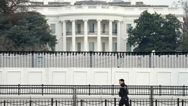 A member of the Secret Service walks along security fence installed around the White House days after supporters of U.S. President Donald Trump stormed the Capitol in Washington, U.S., January 11, 2021. - Sputnik International