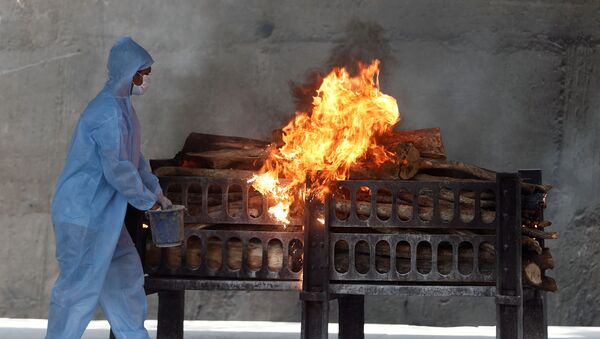 A frontline worker in personal protective equipment (PPE) sprays a flammable liquid on a burning funeral pyre of a man who died from the coronavirus disease  (COVID-19), at a crematorium on the outskirts of Mumbai India, April 15, 2021 - Sputnik International