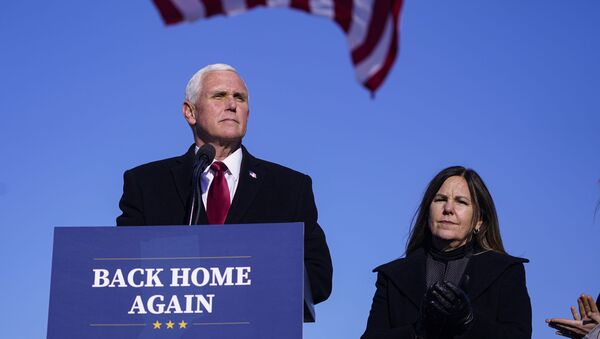 In this Jan. 20, 2021, file phot, former Vice President Mike Pence speaks after arriving back in his hometown of Columbus, Ind., as his wife Karen watches. - Sputnik International