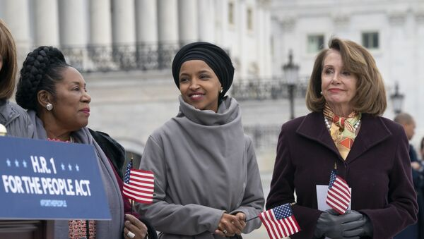 Rep. Ilhan Omar, D-Minn., smiles as she stands between Rep. Sheila Jackson Lee, D-Texas, left, and Speaker of the House Nancy Pelosi, D-Calif., as Democrats rally outside the Capitol ahead of passage of H.R. 1, The For the People Act, a bill which aims to expand voting rights and strengthen ethics rules, in Washington, Friday, March 8, 2019. - Sputnik International