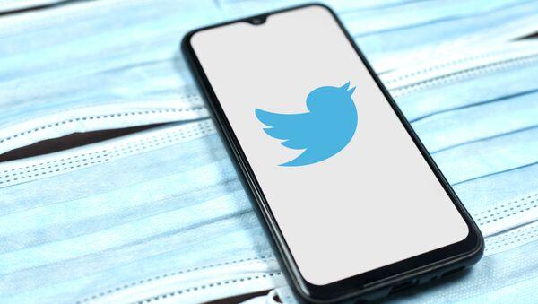 Twitter logo on smartphone screen over the face masks - Sputnik International