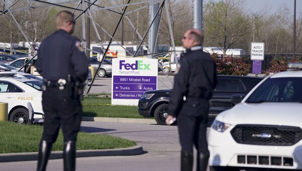 Police stand near the scene where multiple people were shot at the FedEx Ground facility early Friday morning, April 16, 2021, in Indianapolis. A gunman killed eight people and wounded several others before apparently taking his own life in a late-night attack at a FedEx facility near the Indianapolis airport, police said, in the latest in a spate of mass shootings in the United States after a relative lull during the pandemic - Sputnik International