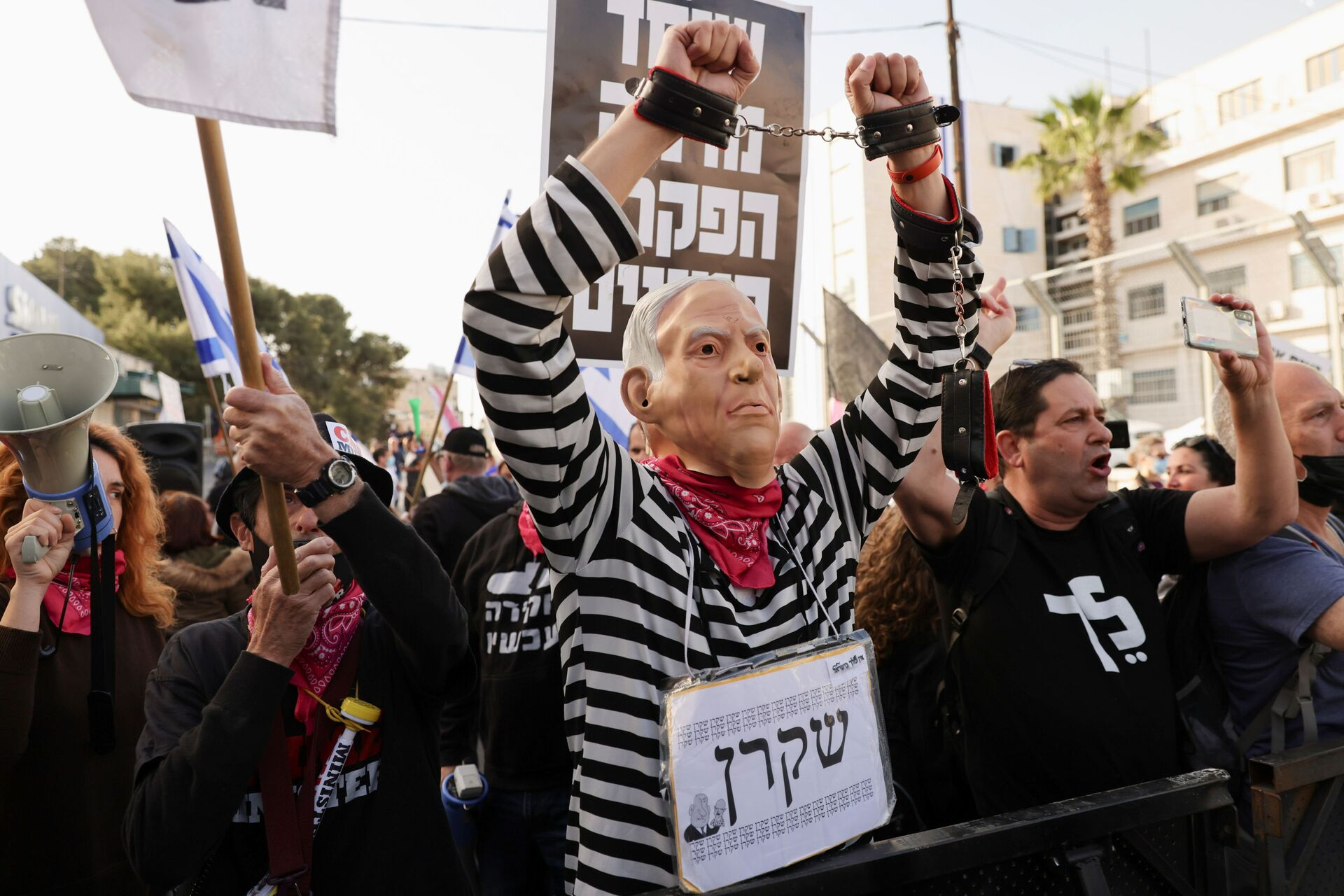 A protester wearing a mask depicting Israeli Prime Minister Benjamin Netanyahu and a sign with the word Liar in Hebrew, gestures during a demonstration against Netanyahu before his corruption trial resumes, near Jerusalem's District Court April 5, 2021. - Sputnik International, 1920, 07.09.2021