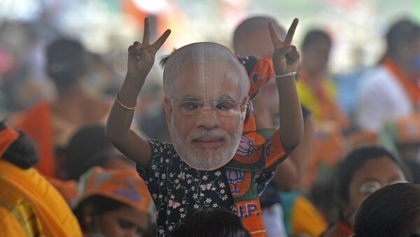 A supporter of Bharatiya Janata Party (BJP) wearing a face cutout of Indian Prime Minister Narendra Modi attends a public rally being addressed by him during the ongoing fourth phase of the West Bengal's state legislative assembly elections, at Kawakhali on the outskirts of Siliguri on April 10, 2021. - Sputnik International