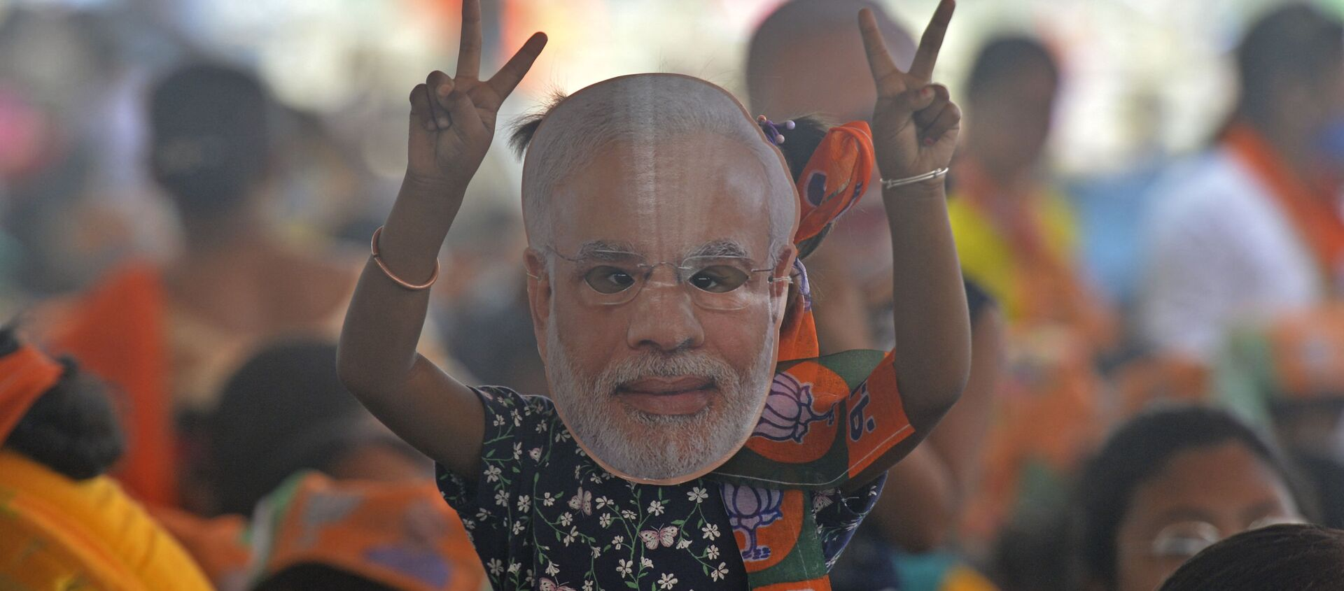 A supporter of Bharatiya Janata Party (BJP) wearing a face cutout of Indian Prime Minister Narendra Modi attends a public rally being addressed by him during the ongoing fourth phase of the West Bengal's state legislative assembly elections, at Kawakhali on the outskirts of Siliguri on April 10, 2021. - Sputnik International, 1920, 07.07.2021